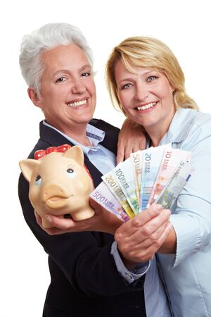 Two senior women with Euro money bills and piggy bank photo