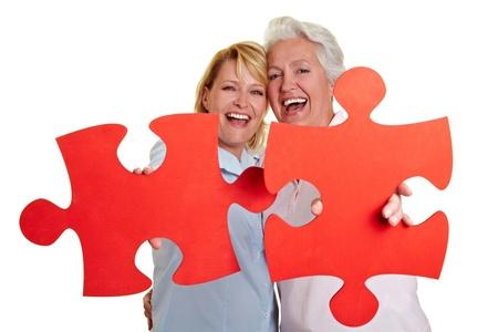 jigsaws: Due donne felici azienda rosso pezzi puzzle Archivio Fotografico