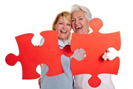 fitting: Two happy women holding red jigsaw puzzle pieces