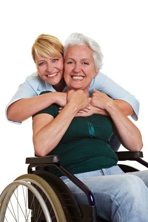 mobility nursing: Happy woman embracing disabled senior woman in wheelchair