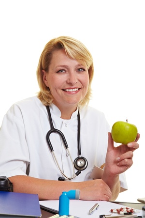 Happy female doctor at desk holding a green apple Stock Photo