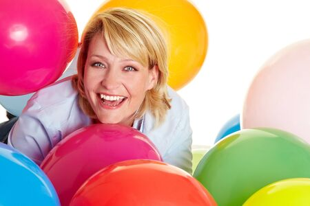 Happy woman celebrating with many colorful balloons