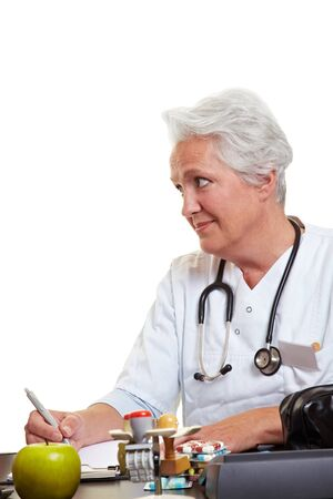 Elderly female doctor at desk listening to patient Stock Photo - 10585644