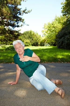 pangs: Senior donna con mal di cuore, seduto in un parco