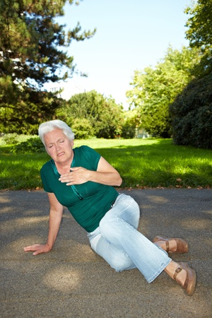 Senior woman with heart pain sitting in a park photo