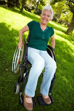 Happy senior woman sitting with wheelchair in nature photo