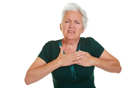 woman chest: Senior woman having coronary and holding hand to her chest Stock Photo