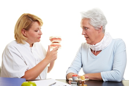 denture: Dentist explaining work to senior woman on teeth model Stock Photo