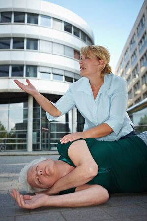 Passerby near helpless senior woman pleading for first aid help photo