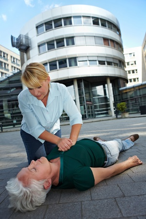 Passerby giving CPR to senior woman as First Aid photo