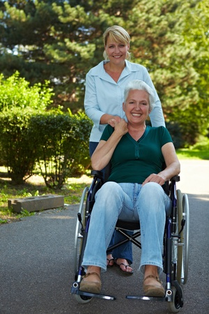 Femme conduisant d�sactiv� femme �g�e en fauteuil roulant dans le parc