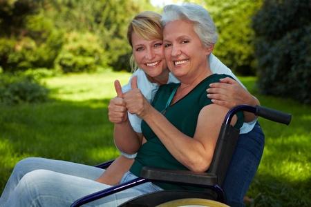 persona en silla de ruedas: Mujer con discapacidad en silla de ruedas y la enfermera de la celebraci�n de los pulgares para arriba Foto de archivo