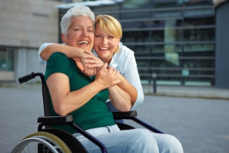 handicapped person: Smiling disabled senior woman in wheelchair with extended care nurse Stock Photo