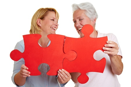 puzzle people: Two happy senior women holding jigsaw puzzle pieces