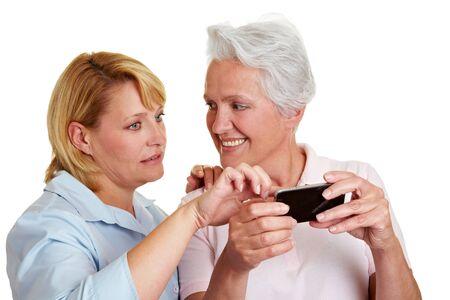 Woman explaining smiling senior woman a smartphone photo