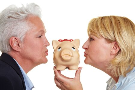 kissing lips: Side view of two senior women kissing a piggy bank Stock Photo