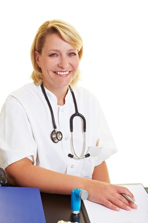 Happy female doctor sitting at office desk Stock Photo - 10585640