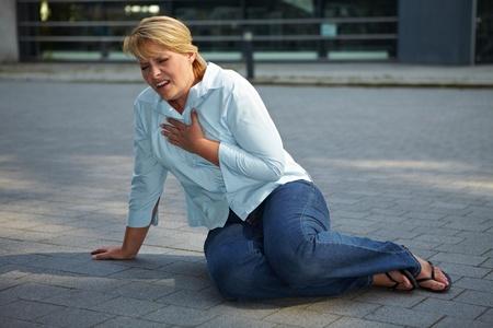 hartaanval: Breathless vrouw zit uitgeput op een stoep Stockfoto
