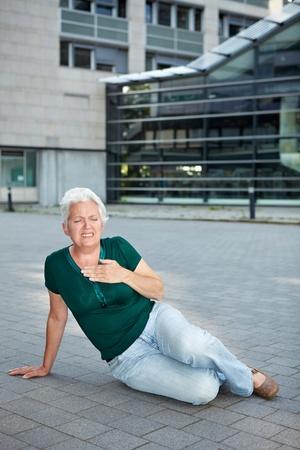 dolor de pecho: Mujer senior con infarto sentado en la acera