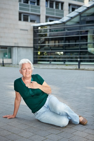 Senior woman with heart attack sitting on sidewalk photo