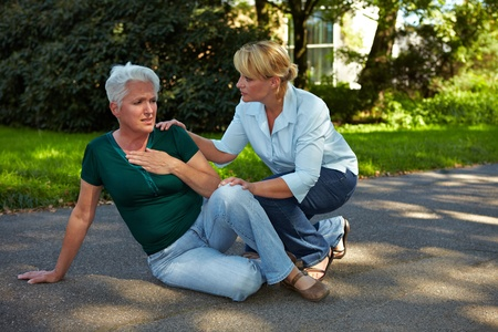palpitations: Passerby helping senior woman with heart attack in park