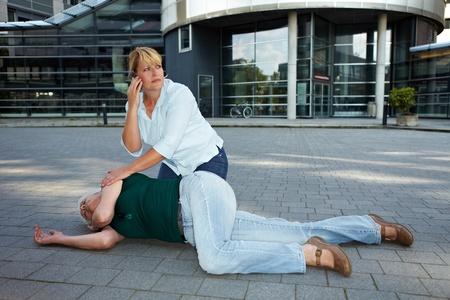 attacco cardiaco: Passante vicino a donna incosciente anziano facendo chiamate di emergenza Archivio Fotografico