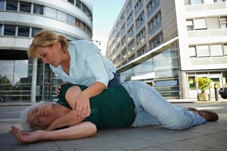 primeros auxilios: Transe�nte haciendo de primeros auxilios y ayudar a la mujer senior en posici�n de recuperaci�n Foto de archivo