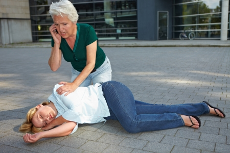 recovery position: Senior woman with helpless woman calling ambulance with cell phone Stock Photo