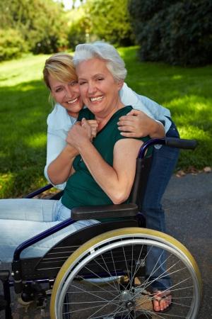 handicap: Infermiera che abbraccia felice donna disabile anziano in sedia a rotelle