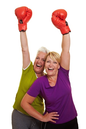 female boxer: Two happy women cheering with red boxing gloves