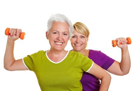 Two happy senior women doing fitness training with dumbbells photo