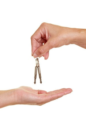Hand offering appartment keys to another hand photo