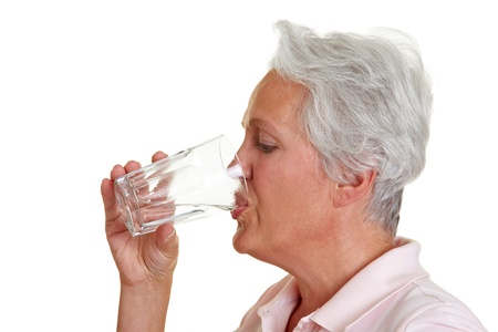 deficiency: Senior woman drinking a glass of fresh water