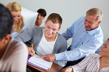 Teacher helping some students in university class