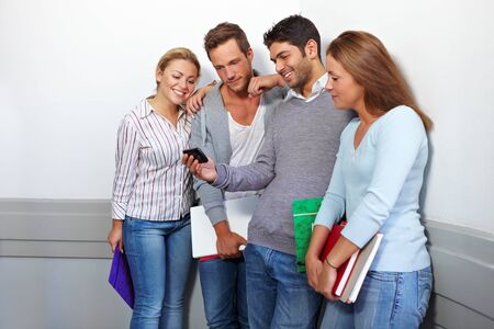 Friends in university looking at a smartphone Stock Photo - 10681800