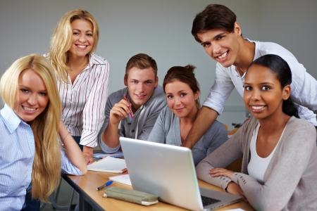 Portrait of group of students around laptop photo