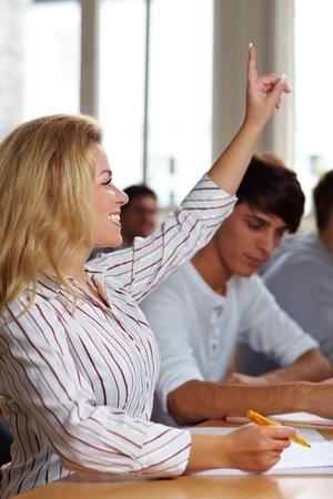 Female student raising her hand in university class photo