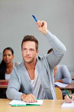 Student giving answer in class with his hand raised photo