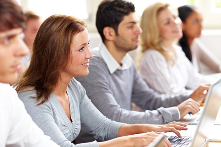 Happy female student with computer in university class photo