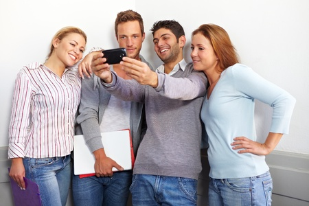 school friends: Teenager friends looking together at a smartphone Stock Photo