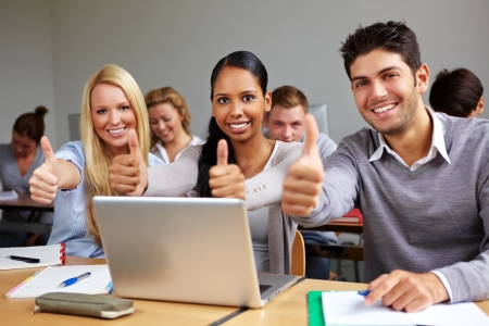 computer training: Successful students in class holding thumbs up
