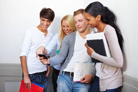 Happy students looking at photos on smartphone Stock Photo - 10681773