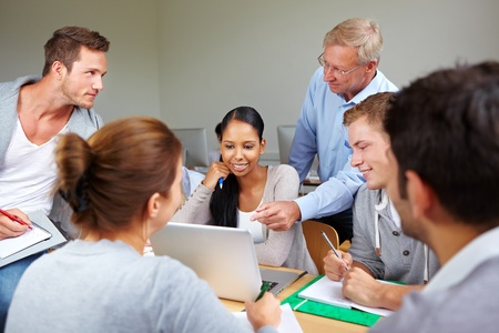 computer lessons: Teacher with students together in a college class Stock Photo
