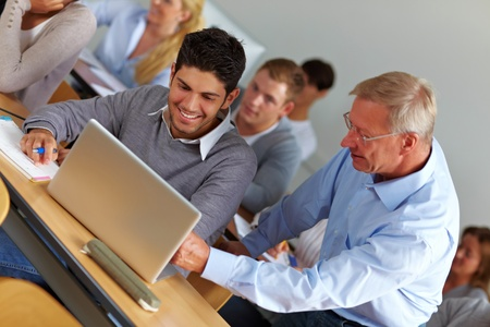 lecturer: Elderly teacher giving assistance in university class Stock Photo