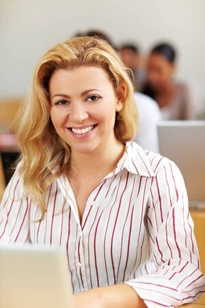 Smiling female student at laptop in university class photo