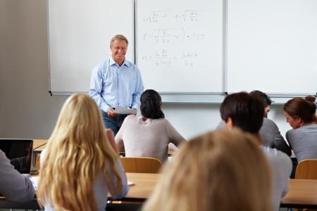 salon de clases: Profesor en la universidad frente a una pizarra Foto de archivo