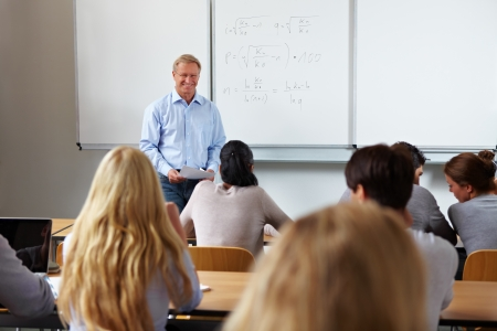 students in classroom: Teacher at university in front of a chalkboard