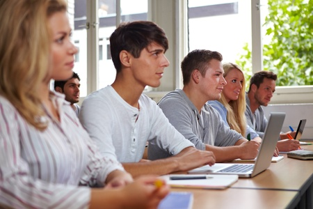 College students with laptops listening in class photo