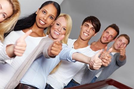 Happy smiling Teens ihre Daumen halten
