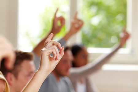 query: Many raised fingers in class at university Stock Photo